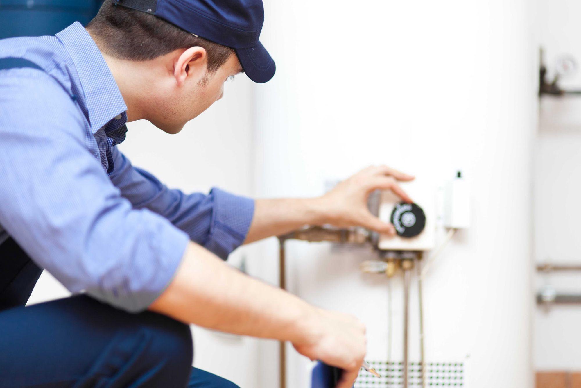Plombier qui travaille sur un chauffe-eau | Plombier | Plomberie Lafleur | Montréal