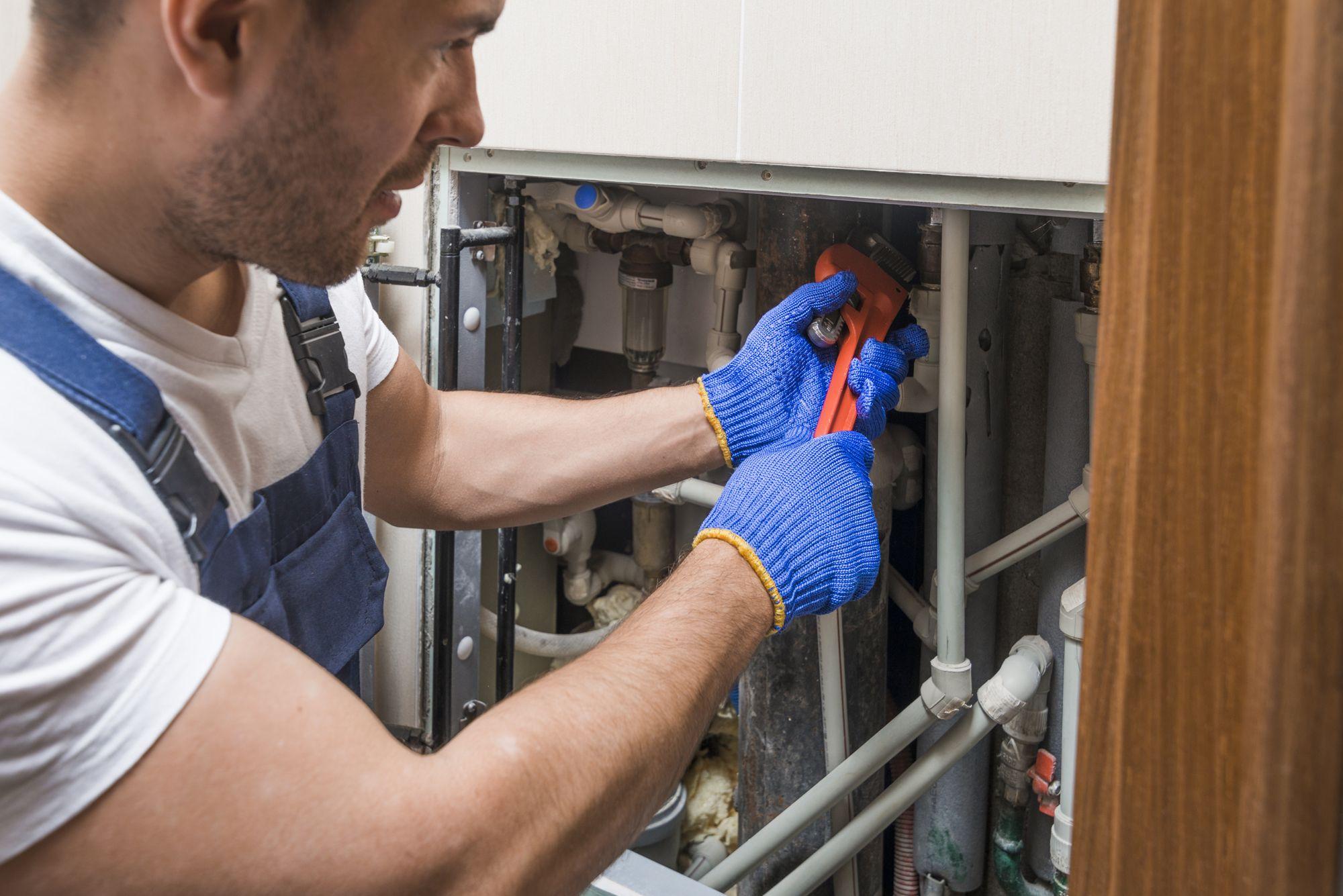 Plombier qui travaille dans un panneau rempli de tuyaux |Plombier | Plomberie Lafleur | Montréal