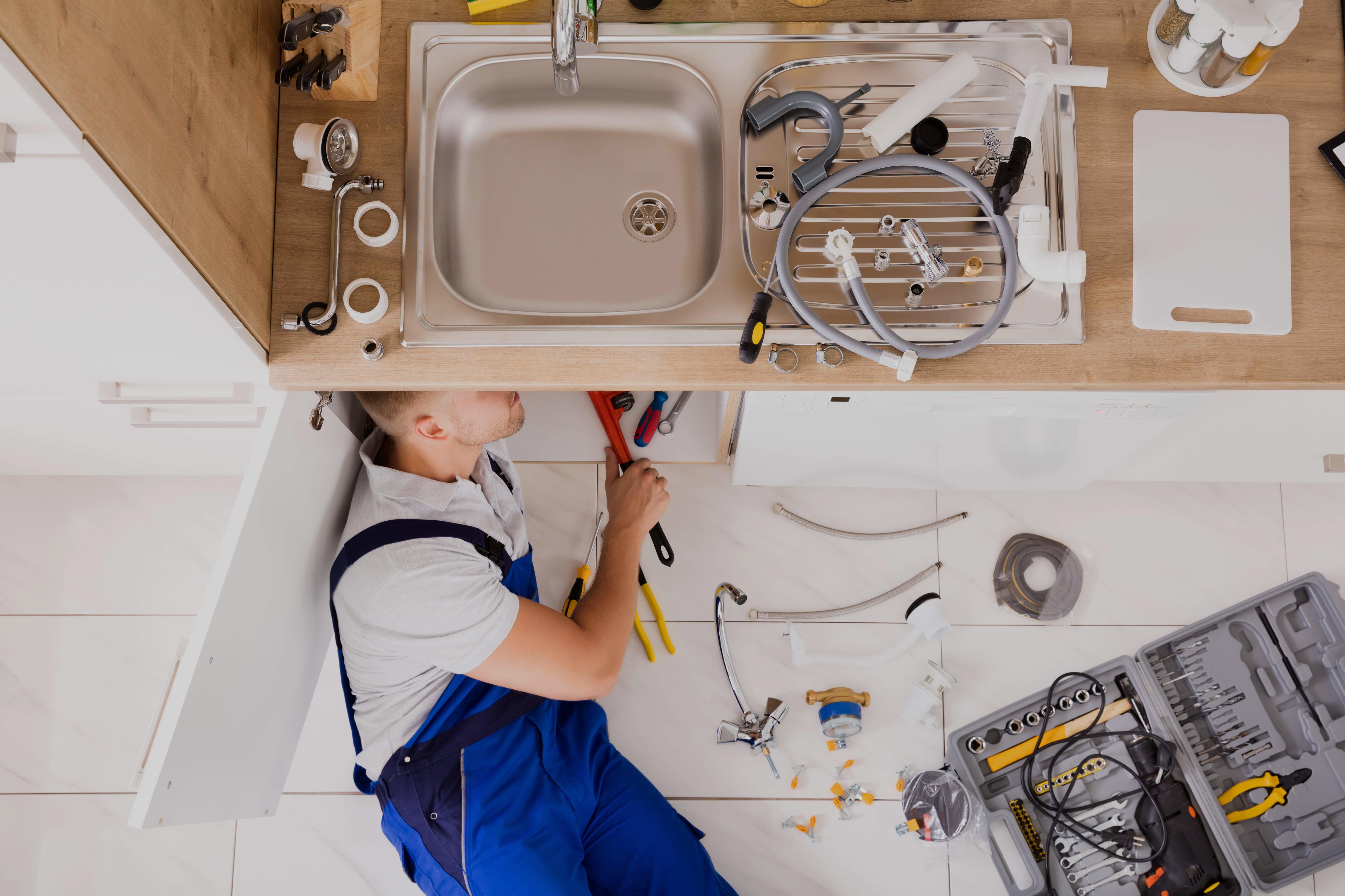 Plombier qui travaille sous un lavabo |Plombier | Plomberie Lafleur | Montréal